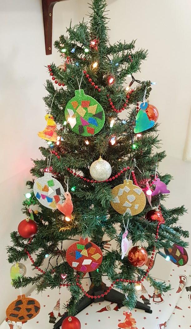 Karácsonyfa a gyerekek által készített alkotásokkal a családi bölcsiben