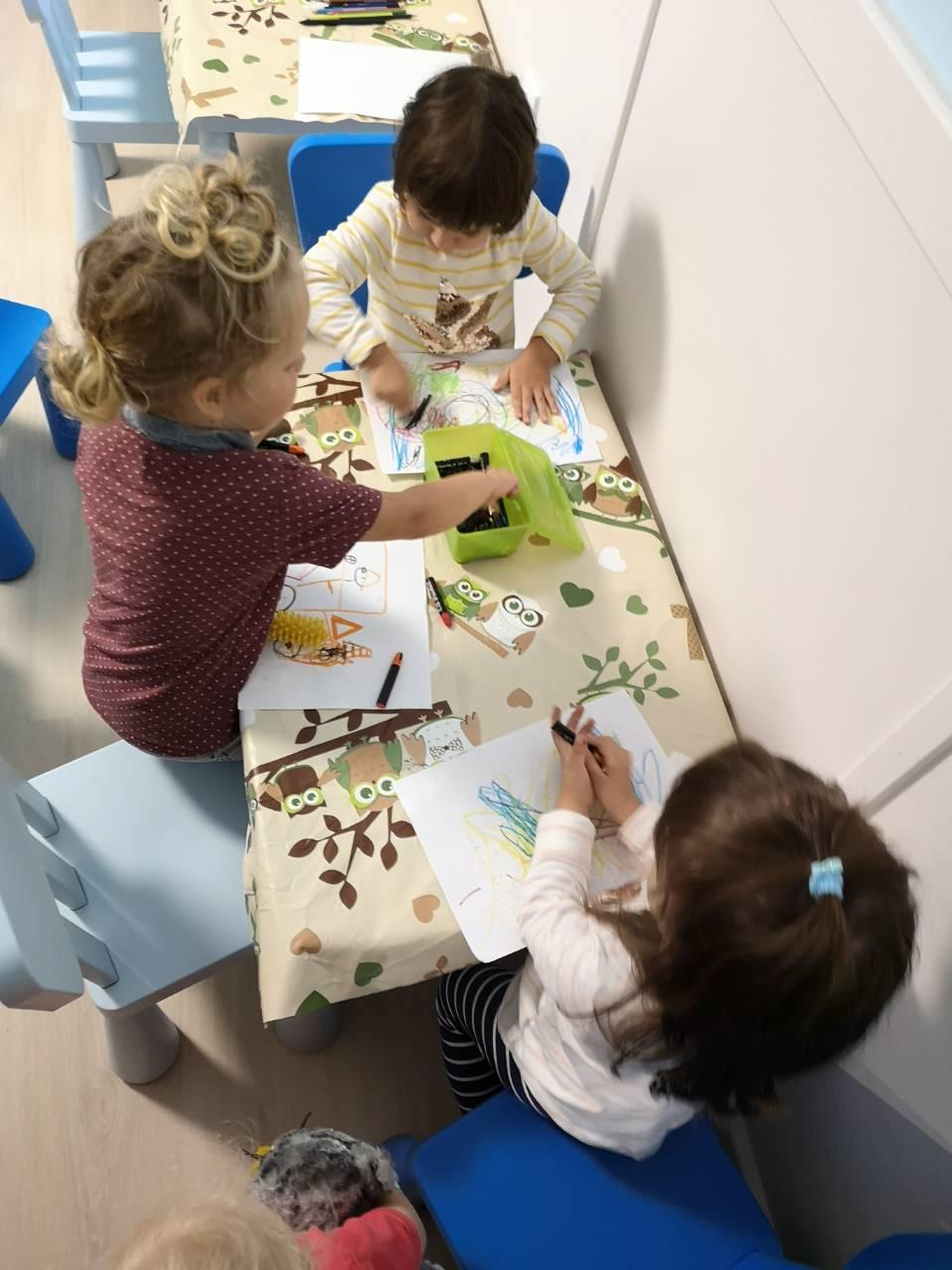 Krétával rajzoló gyerekek a családi napköziben