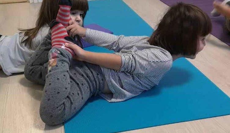 Nyújtó gyakorlatot bemutató kislány a családi napköziben
