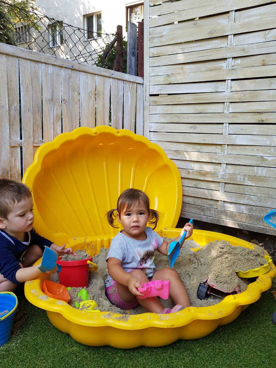 Homokozó gyerekek a családi napközi udvarán